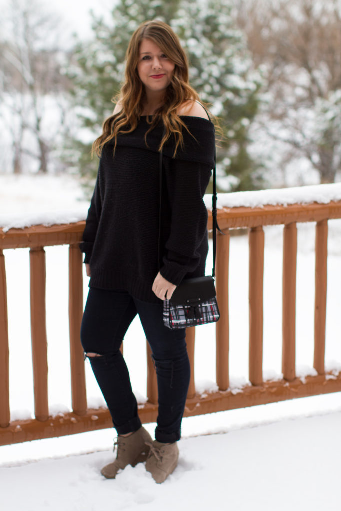 Standing in the snow in an OTS black sweater, Frame denim, TOMS booties and a Vera Bradley crossbody bag